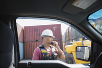 Male worker using walkie-talkie outside truck in industrial container yard 11096052740| 写真素材・ストックフォト・画像・イラスト素材|アマナイメージズ
