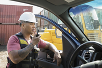 Male worker using walkie-talkie at truck in industrial container yard 11096052742| 写真素材・ストックフォト・画像・イラスト素材|アマナイメージズ