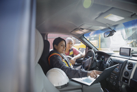Workers using laptop and talking in truck in industrial container yard 11096052758| 写真素材・ストックフォト・画像・イラスト素材|アマナイメージズ