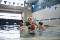 Smiling young women swimmers talking in swimming pool 11096053006| 写真素材・ストックフォト・画像・イラスト素材|アマナイメージズ