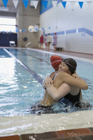 Smiling young women swimmers hugging in swimming pool 11096053012| 写真素材・ストックフォト・画像・イラスト素材|アマナイメージズ
