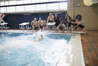 Swim team cheering teammate swimming in swimming pool at competitive swim meet 11096053033| 写真素材・ストックフォト・画像・イラスト素材|アマナイメージズ