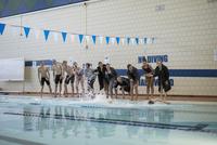 Swim team cheering teammate swimming in swimming pool at competitive swim meet 11096053035| 写真素材・ストックフォト・画像・イラスト素材|アマナイメージズ