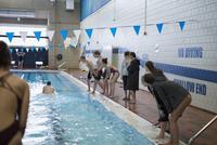 Swim team cheering teammate swimming in swimming pool at competitive swim meet 11096053037| 写真素材・ストックフォト・画像・イラスト素材|アマナイメージズ