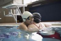Female swimmers hugging in swimming pool 11096053083| 写真素材・ストックフォト・画像・イラスト素材|アマナイメージズ
