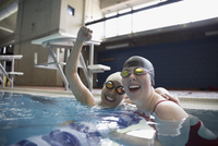 Portrait smiling female swimmers cheering and celebrating in swimming pool 11096053084| 写真素材・ストックフォト・画像・イラスト素材|アマナイメージズ