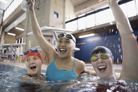Portrait smiling female swimmers cheering and celebrating in swimming pool 11096053085| 写真素材・ストックフォト・画像・イラスト素材|アマナイメージズ