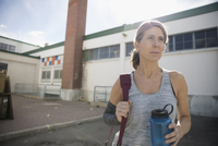 Confident, determined woman with water bottle in parking lot post workout 11096053145| 写真素材・ストックフォト・画像・イラスト素材|アマナイメージズ