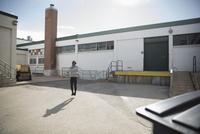 Man jumping rope in sunny parking lot 11096053147| 写真素材・ストックフォト・画像・イラスト素材|アマナイメージズ