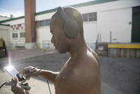Bare chested man with headphones and mp3 player listening to music and holding jump rope, exercising in sunny parking lot 11096053149| 写真素材・ストックフォト・画像・イラスト素材|アマナイメージズ