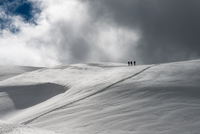 Three skiers on snow covered hill, Italy