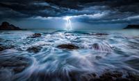 Lightning striking over sea against overcast sky