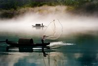 Fisherman on boat throwing net