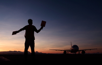 Silhouette of man signaling to aircraft at dusk
