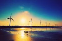 Silhouette of wind turbines on beach at sunset