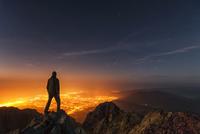 Man standing on mountain peak at night and looking down at illuminated city, Sinite Kamani Park, Balkan Mountains, Sliven, Bulga
