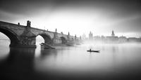 Charles Bridge and person in boat in fog, Praha, Czech Republic