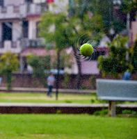 Wet tennis ball splashing water in air