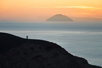 Silhouettes of two people looking at view from cliff
