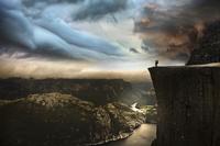 Man standing on Preikestolen cliff looking at view, Norway