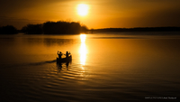 Two people canoeing on lake at sunset