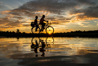 Silhouettes of man riding bicycle with child on back seat at sunset