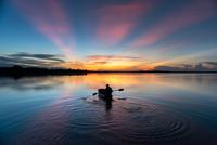 Silhouette of men paddling in kayak on lake at sunset