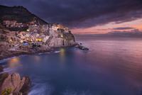 Town on coastline rocks at dusk