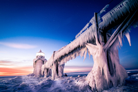 Ice-covered lighthouse at sunset