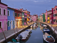 Multicolored houses alongside canal at night