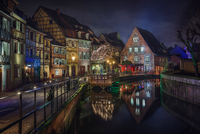 Illuminated buildings in old town reflecting in river at night, Colmar, France