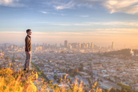 Man standing on rock and looking at city, San Francisco, California, USA