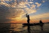 Fishermen on boat throwing fish net onto water