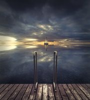 Metal ladder on wooden jetty and sailboat in background at sunset