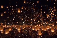 People launching sky lanterns during Yi Peng Festival in Chiang Mai, Thailand