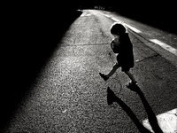 Boy (4-5) with ball crossing street