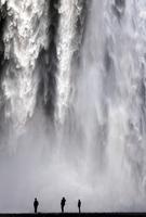 Silhouettes of three people admiring waterfall, Skogafoss, Iceland