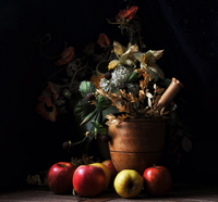 Apples and flower pot on table