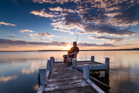 Man sitting on chair and fishing from jetty