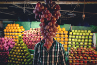 Man standing behind bunch of red grapes