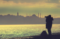 Silhouette of man photographing townscape at dusk
