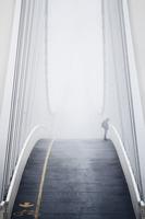Silhouette of man standing alone on bridge in mist