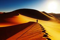 Silhouette of man walking on sand dune, Sahara, Algeria
