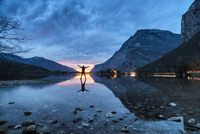 Silhouette of person with arms raised by Lake Toblino at sunset