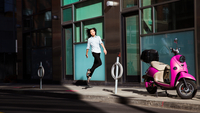 Woman jumping on street next to pink motor scooter
