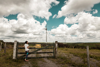 Young woman looking at view of rural area with wind turbine, Palmas, Tocantins, Brazil