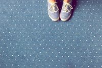 Feet on blue carpet with polka dots
