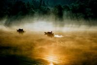 Two boats swimming through morning mist on Dongjiang Lake, Chenzhou, Hunan Province, China