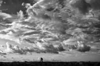 Silhouettes of two men walking under dramatic sky, Tel Aviv, Israel