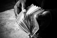 Elderly man holding bunch of banknotes